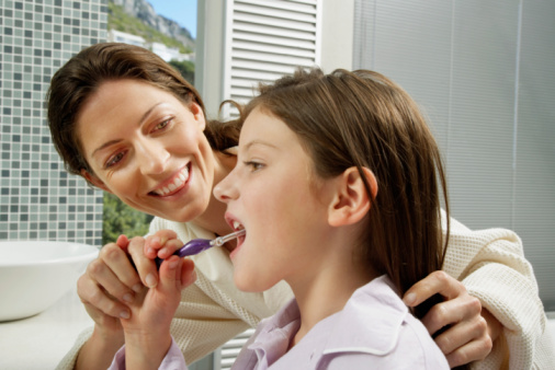 Mother helping Daughter to Brush Teeth